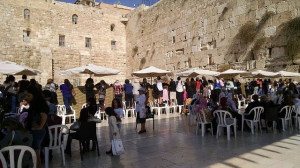 At the Western Wall, women lean over the barrier to the mens' side to see their sons' bar mitzvahs.