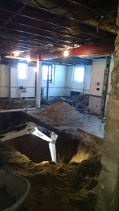 Towards the back, you can see where the bathrooms have been excavated. The big pile of stuff in the back right is old plumbing.
