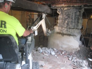 """It took over a day to remove the """"oil tank room"""" wall because it was poured concrete with steel rebar. The concrete diamond saw blade  was employed to cut through this foundation wall initially, then the Bob Cat with an jack hammer chipped away at it for many hours more. Note the steel beam was temporarily placed to support the ceiling while the wall is removed and then a support column is built in the middle between the elevator shaft on the left and the new hallway on the right."""